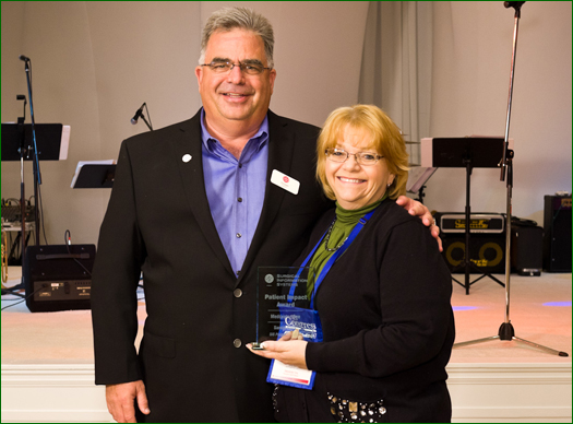 On behalf of Medcenter One, Sandy Fleck accepts the Patient Impact Award from Ed Daihl, CEO of Surgical Information Systems (SIS). The Patient Impact Award is one of a number of Perioperative Leadership Awards SIS presents at its annual user conference.
